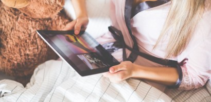 Girl Holding an iPad in Bed