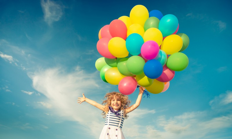 Happy child jumping with colorful toy balloons