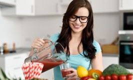 Happy young woman pouring vegetable smoothies
