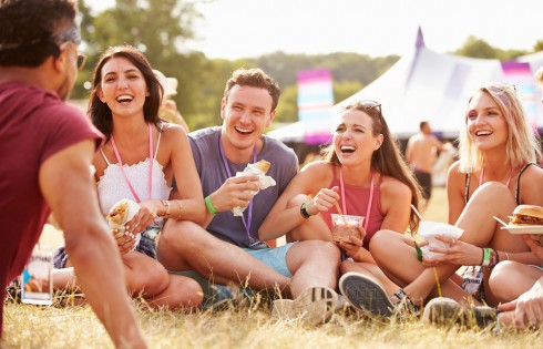 Friends sitting on grass and eating at music festival